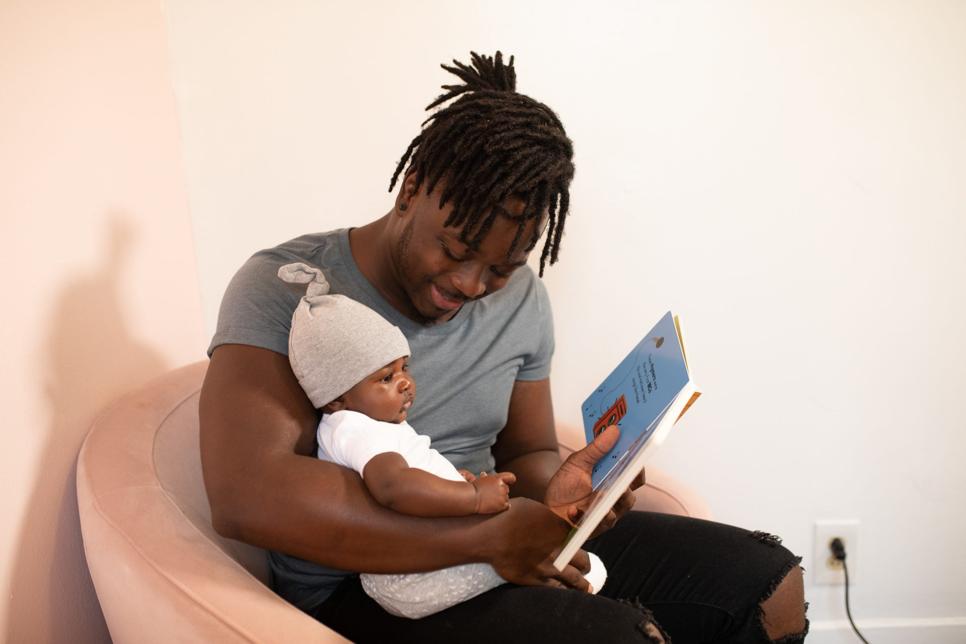man and baby reading a book